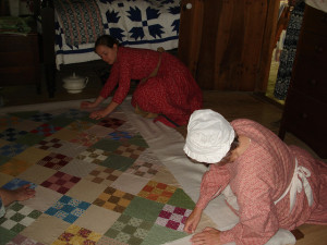Interpreters in period clothing piecing together a quilt during the 2015 Quilting Bee. Photo provided by Cindy Earls