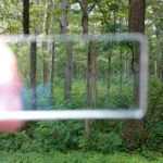 """Looking through a prism to tell if surrounding trees are within a """"plot."""" Photo by Yvonne Helton"""